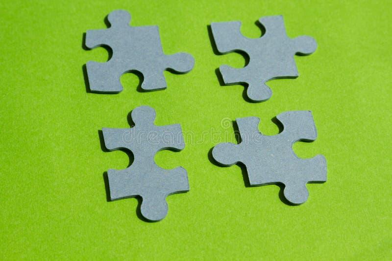 Pedazos del rompecabezas en fondo verde claro fotografía de archivo libre de regalías