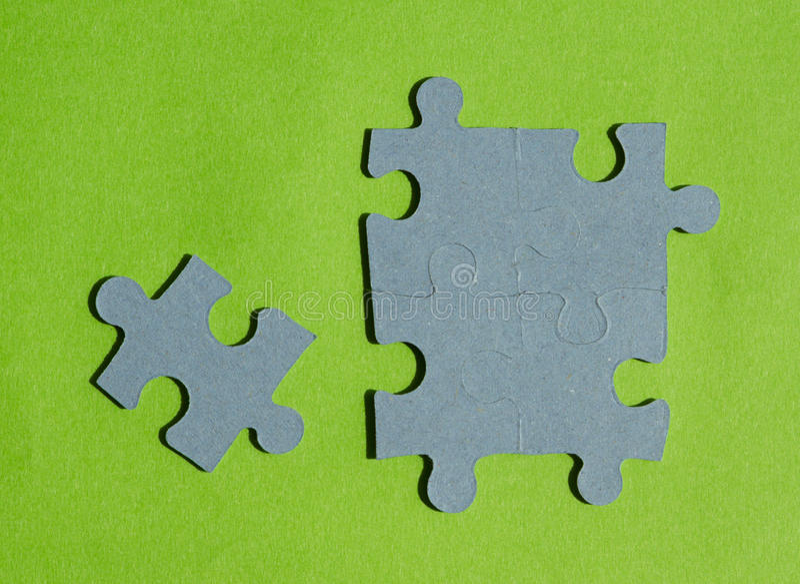 Pedazos del rompecabezas en fondo verde claro fotos de archivo