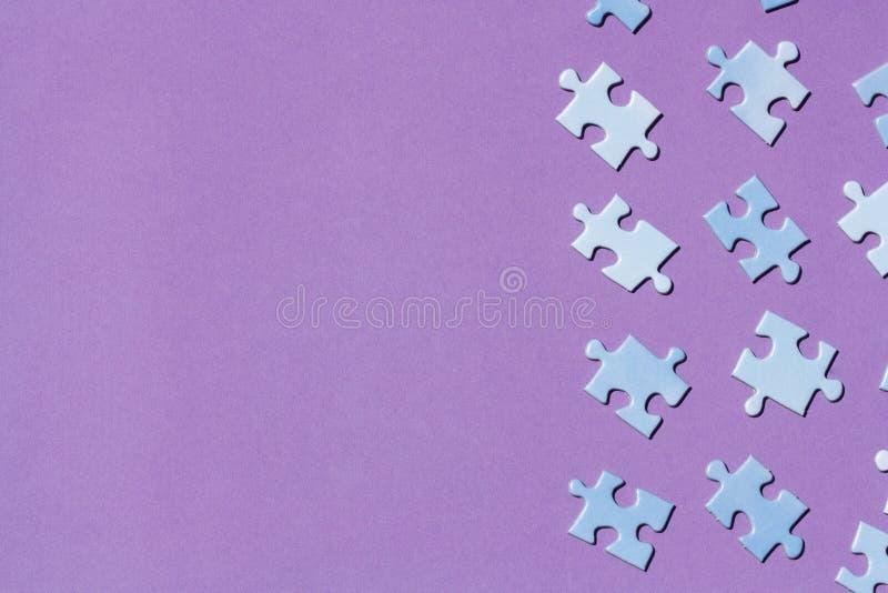 Pedazos del rompecabezas en un fondo púrpura imagen de archivo