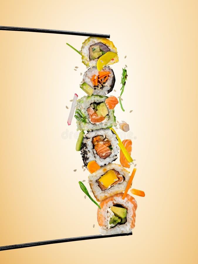 Pedazos del sushi puestos entre los palillos, en fondo coloreado ilustración del vector