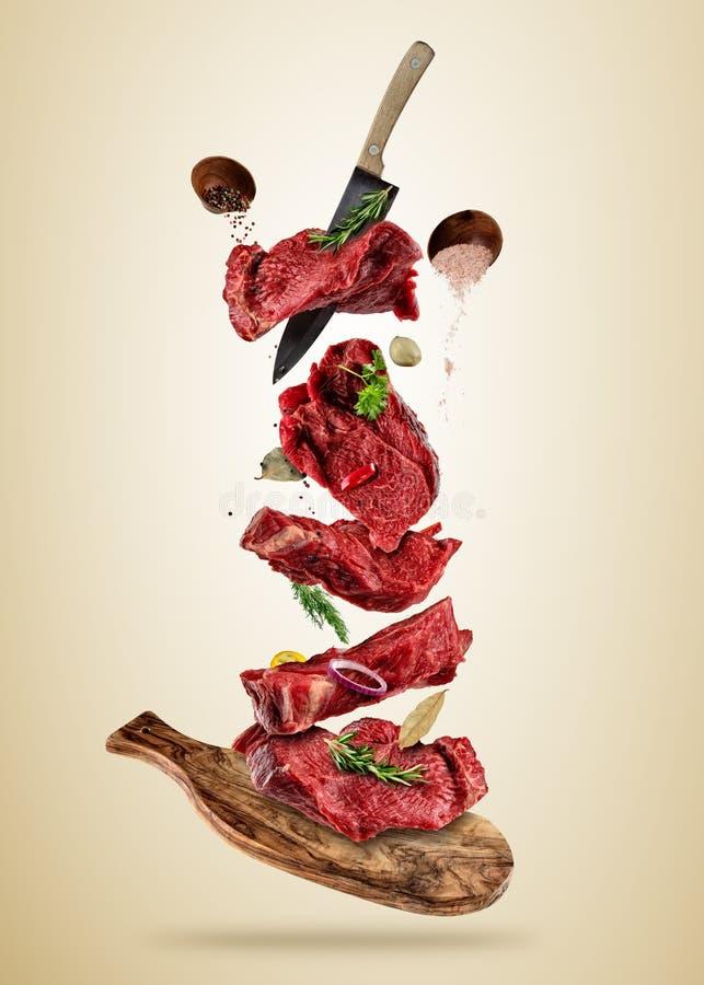 Pedazos del vuelo de filetes de carne de vaca crudos de la tabla de cortar stock de ilustración