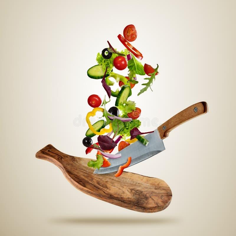 Pedazos del vuelo de verdura con la tabla de cortar y el cuchillo ilustración del vector