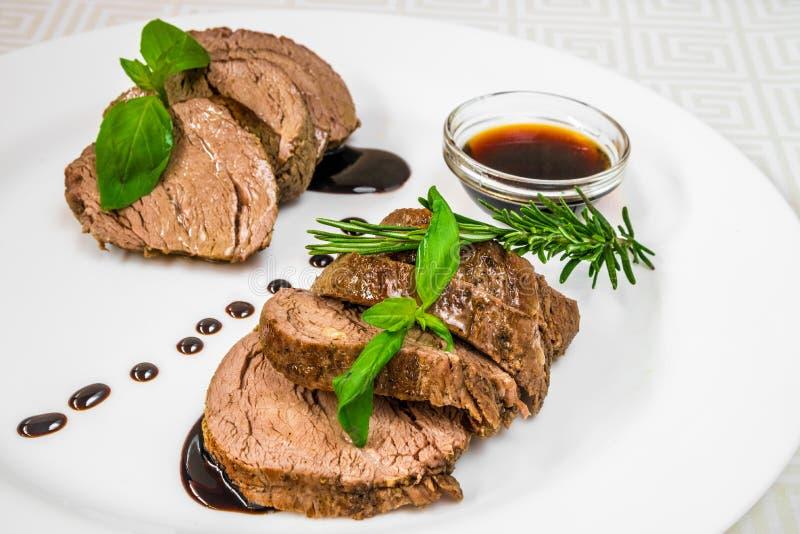 Pedazos deliciosos, apetitosos de carne asada con las hierbas y salsa, en una placa blanca Marco horizontal imagen de archivo