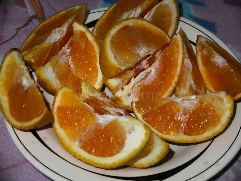 Pedazos frescos del corte de las naranjas en un plato imagenes de archivo