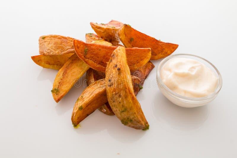 pedazos fritos apetitosos de la patata con ajo y sal, con la salsa blanca en una placa imagen de archivo