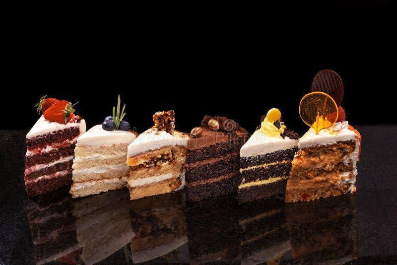 Pedazos grandes clasificados de diversas tortas: chocolate, frambuesas, fresas, nueces, arándanos Pedazos de tortas en a foto de archivo