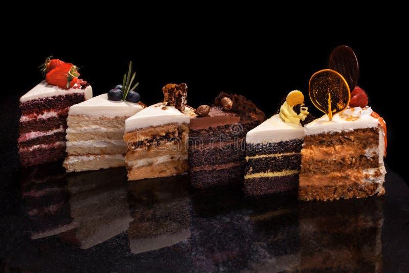 Pedazos grandes clasificados de diversas tortas: chocolate, frambuesas, fresas, nueces, arándanos Pedazos de tortas en a fotos de archivo