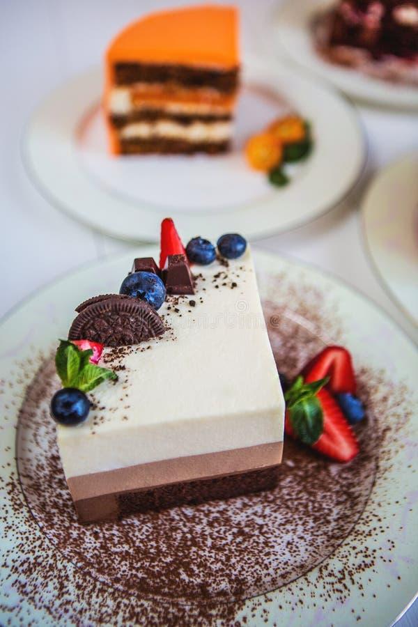 Pedazos grandes clasificados de diversas tortas: tres chocolate, zanahoria, fresa, chocolate Las tortas se adornan con las bayas imagen de archivo