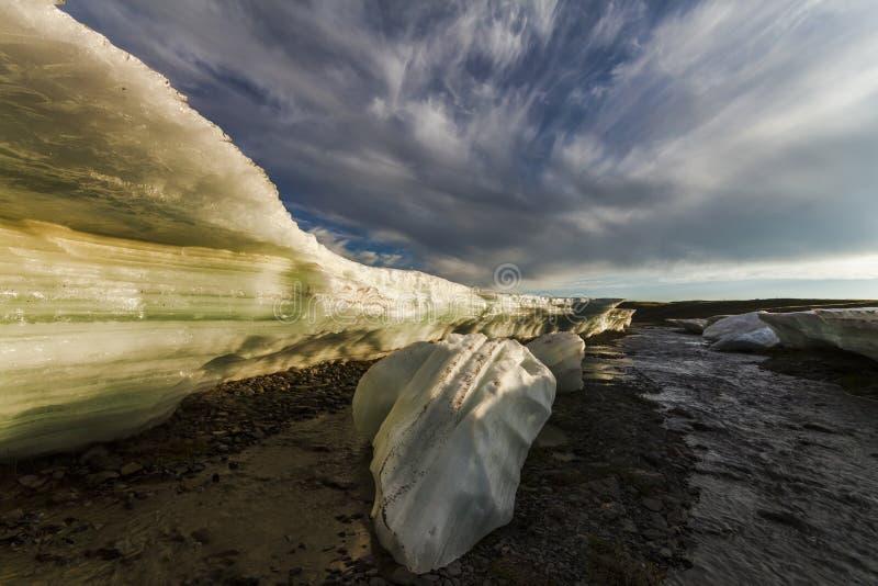 Pedazos grandes de hielo de fusión en una playa imagenes de archivo