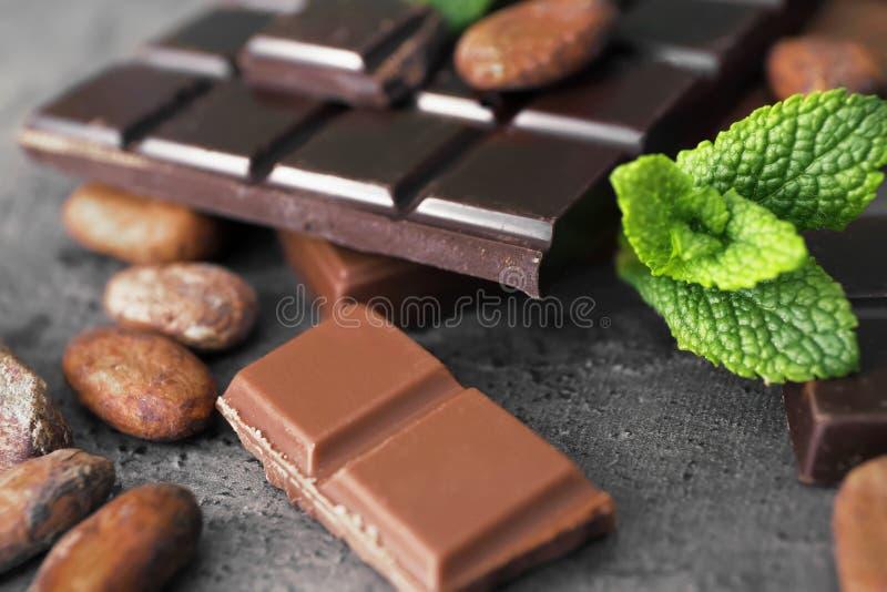 Pedazos granos sabrosos del chocolate y de cacao en la tabla, primer foto de archivo