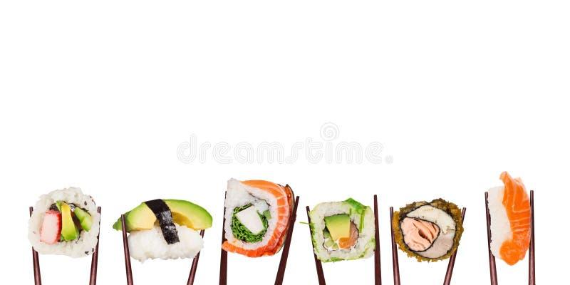 Pedazos japoneses tradicionales del sushi puestos entre los palillos, separados en el fondo blanco fotografía de archivo libre de regalías