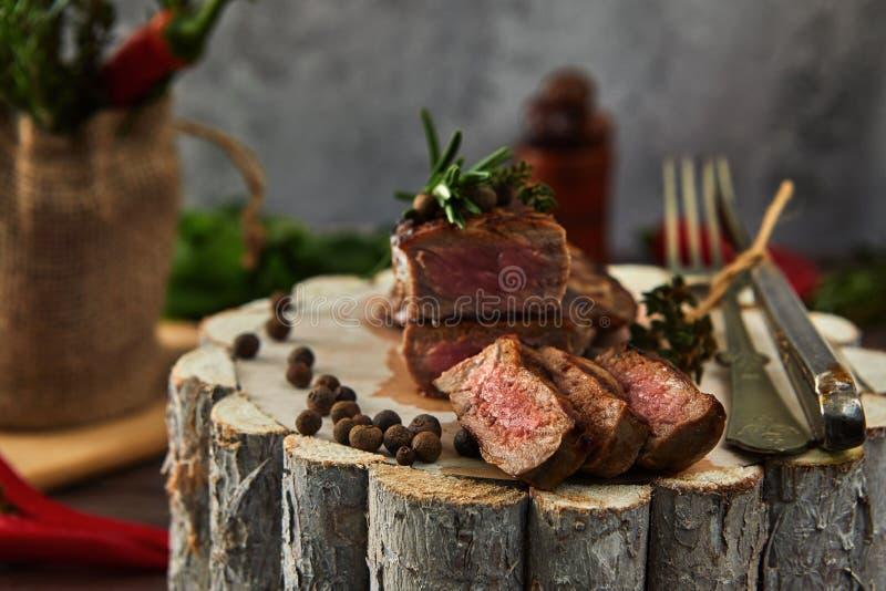 Pedazos medios jugosos de filete de carne de vaca del ojo de la costilla en una cacerola en un tablero de madera con una bifurcac imagen de archivo