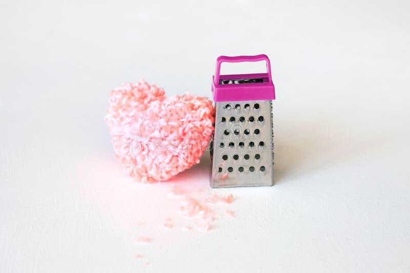 Pedazos mullidos rosados del corazón y del hilo en el rallador Desintegración dura, imagen de archivo
