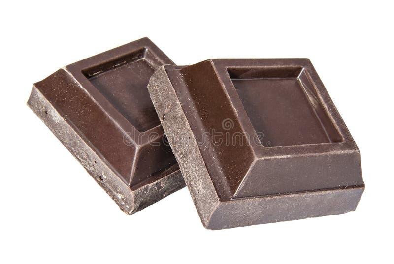 Pedazos oscuros del cuadrado del chocolate en un fondo blanco imagen de archivo