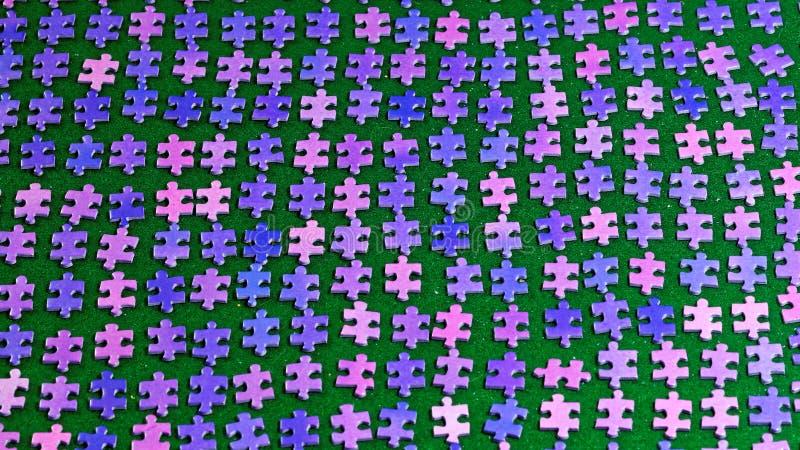 Pedazos púrpuras del rompecabezas clasificados en un mantel verde imágenes de archivo libres de regalías