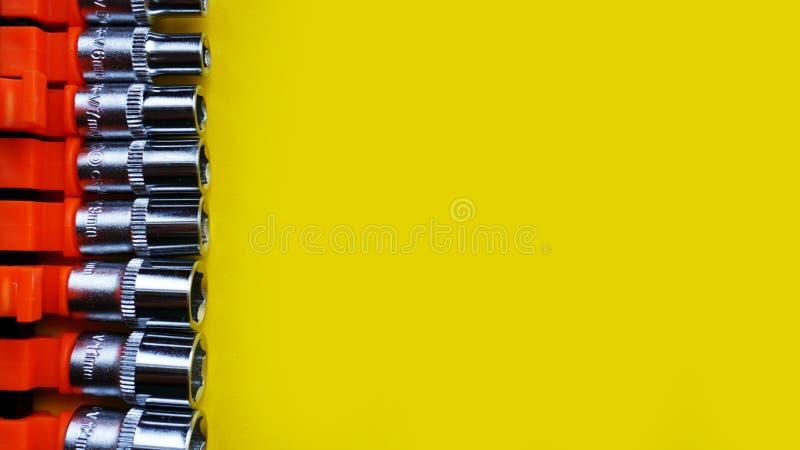 Pedazos principales de la llave para el destornillador y otras herramientas en fondo amarillo brillante imagenes de archivo