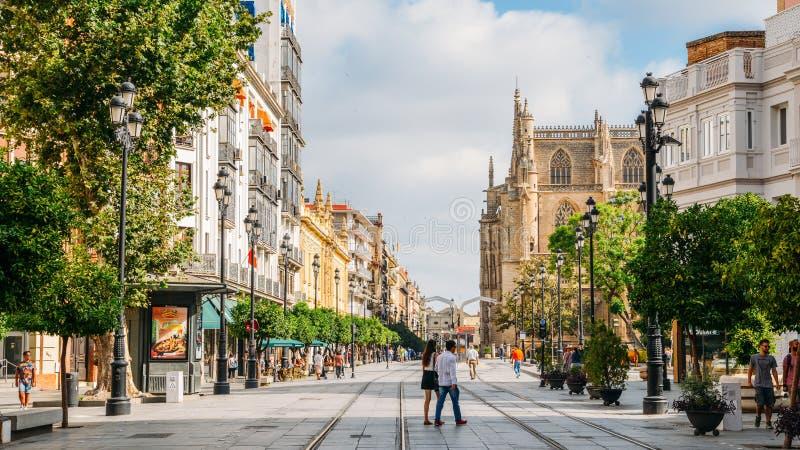 Pedestres em Constitution Avenue com a catedral icónica de Sevilha no fundo fotografia de stock