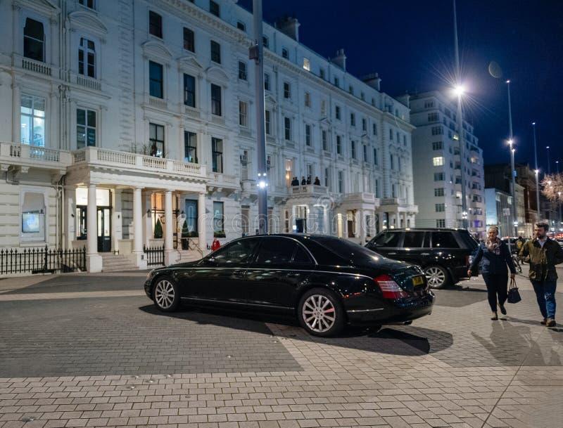 Pedestres que andam ao lado do pa luxuoso da limusina de Mercedes-Maybach fotografia de stock