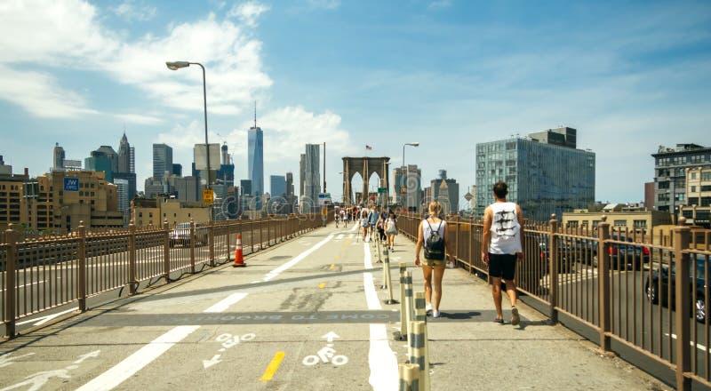 Pedestres que andam pela ponte de Brooklyn em New York City fotografia de stock