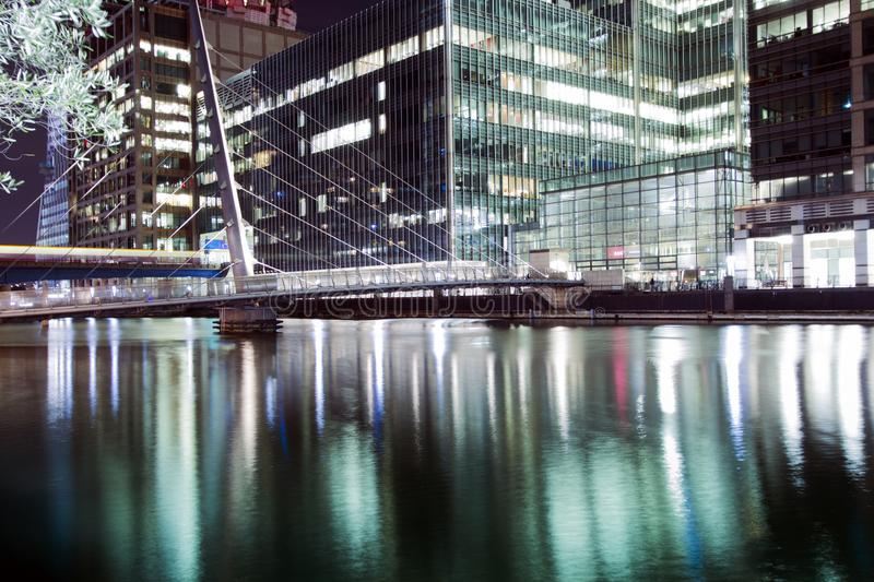 The pedestrian bridge connecting Millwall to Canary Wharf under night. stock photo