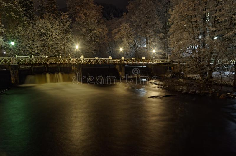 Pedestrian bridge over small dam by night. This small bridge is located in the city Bad Lauterberg, in Harz mountains national park, Germany royalty free stock photography
