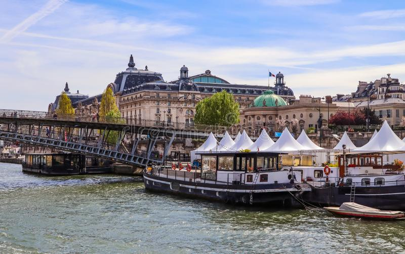 Pedestrian bridge Passerelle Léopold-Sédar-Senghor over Seine river, boats and historic buildings of Paris France.  stock image