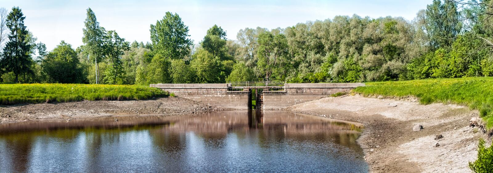 Pedestrian bridge on the pond in the park in early spring in clear weather royalty free stock photo