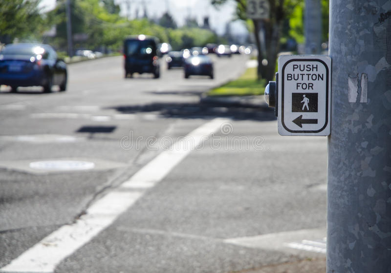 Pedestrian cross walk sign and button on busy street with cars a royalty free stock images