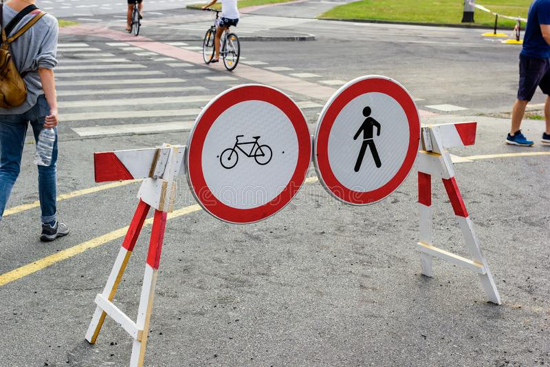 Pedestrian crossing with forbidden crossing signs for pedestrians and cyclists. With pedestrians walking around it stock image