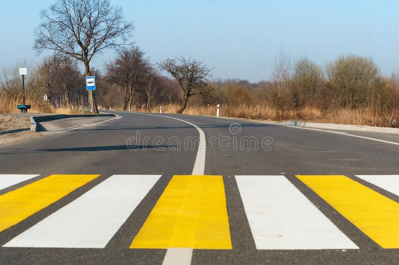 Pedestrian crossing outside the city, white yellow markings on the road royalty free stock images