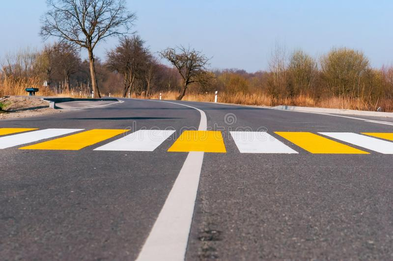 Pedestrian crossing outside the city, white yellow markings on the road. White yellow markings on the road, pedestrian crossing outside the city stock photography