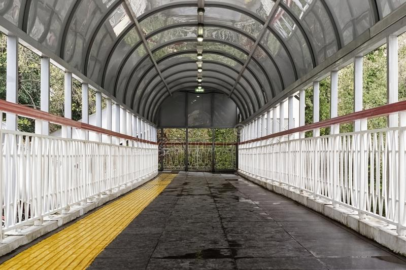 Pedestrian crossing over the road-bridge with roof with yellow track for the blind stock photography