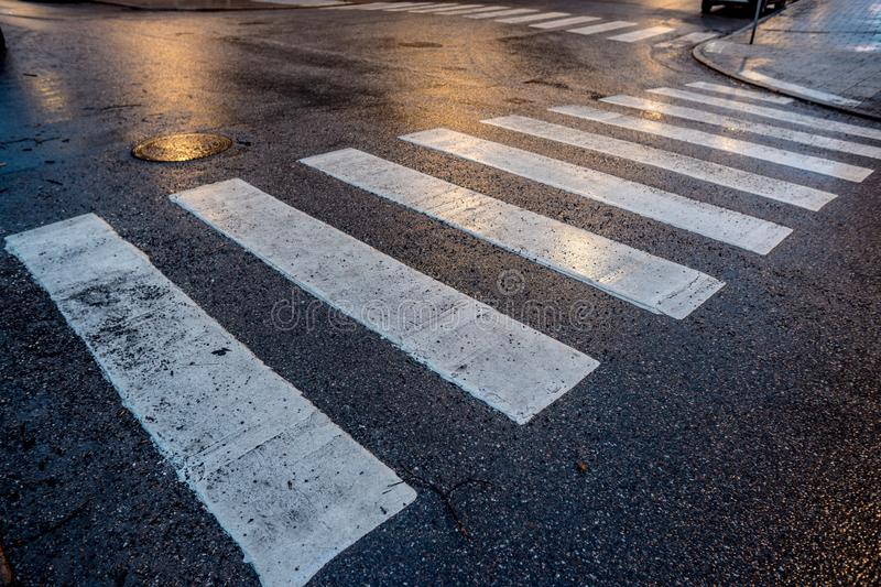 Pedestrian crossing over wet asphalt royalty free stock images