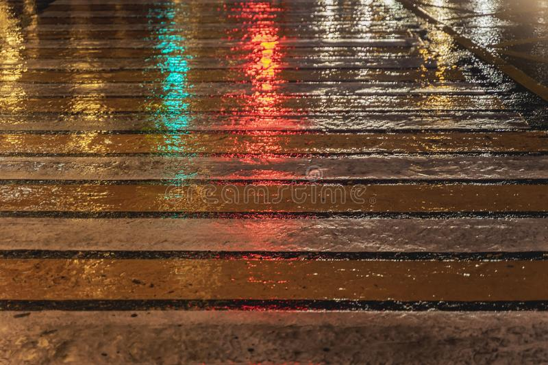Pedestrian crossing in rainy evening. Road markings on asphalt with bright reflected from traffic lights. Striped yellow. Pedestrian crossing in rainy evening stock photos