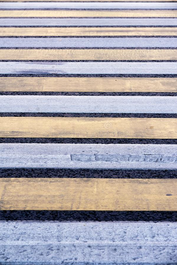 Pedestrian crossing. Road markings on asphalt. Striped blue and yellow background and texture stock photos