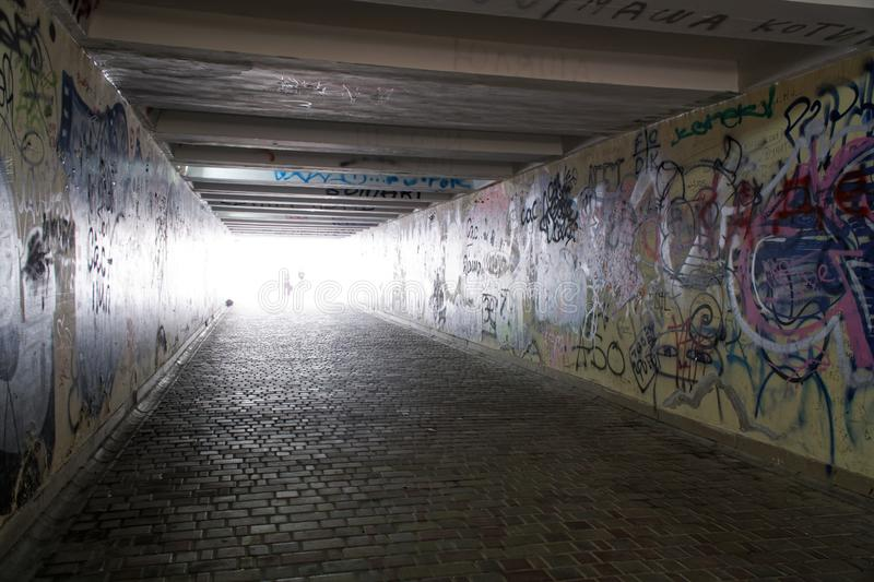 Pedestrian crossing tunnel, Dark and long underground passage with light stock photography