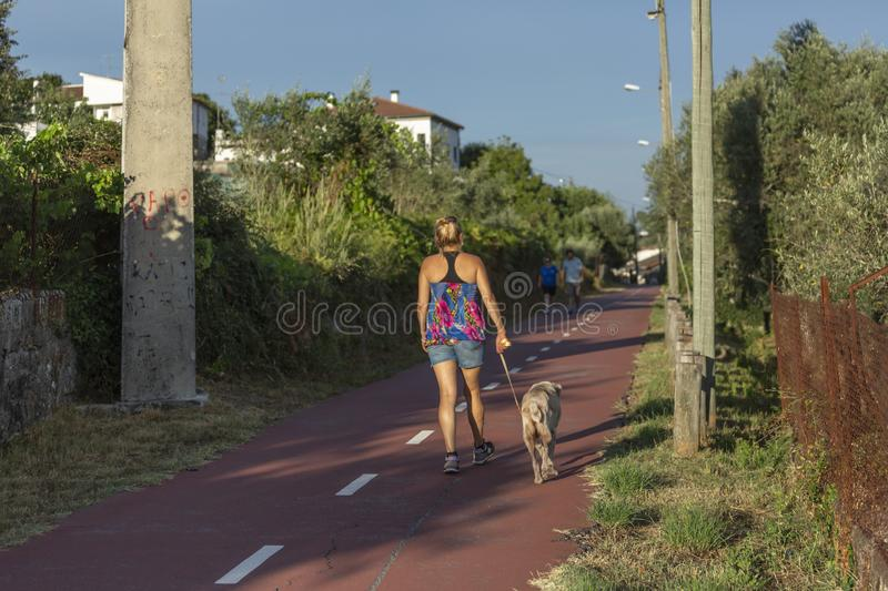 Pedestrian and cycle eco path, in Viseu, Portugal. Pedestrian and cycle eco path, woman with a dog and people walking, background and vegetation, in Viseu royalty free stock image