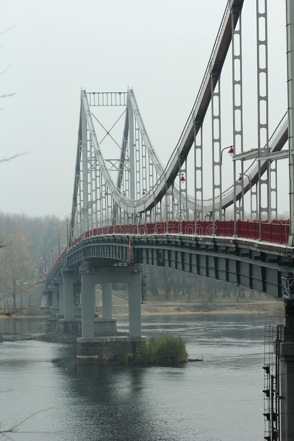 Pedestrian empty bridge in Kyiv on a rainy foggy day royalty free stock photography