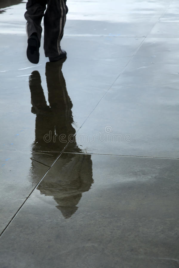 Inclement Winter Pedestrian. A pedestrian's reflection on the wet concrete pavement on an inclement and wet winter day stock photography