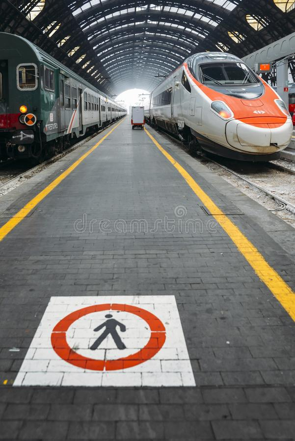 Pedestrian sign on edge of platform at Milan`s Central Station, a major rail hub in northern Italy with connections. Milan, Italy - Jan 28, 2017: Pedestrian sign royalty free stock images