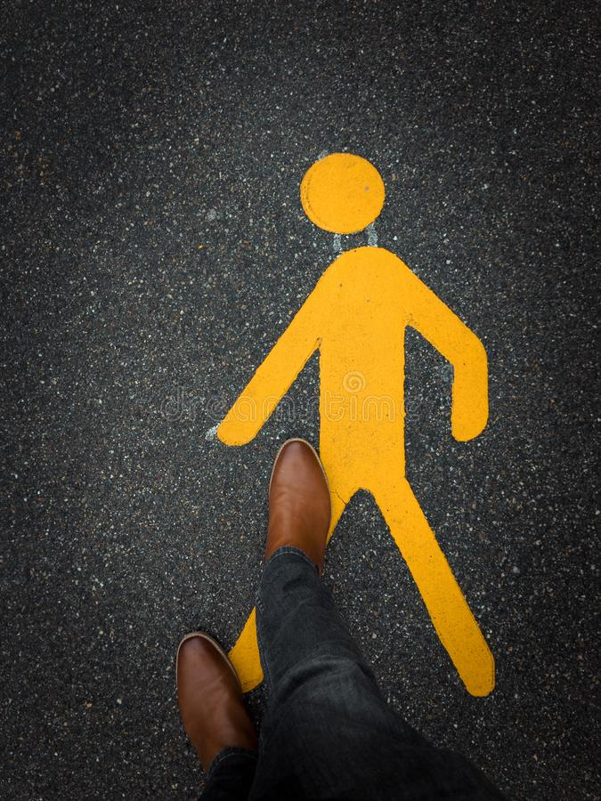 Pedestrian sign on pavement with feet stock photos