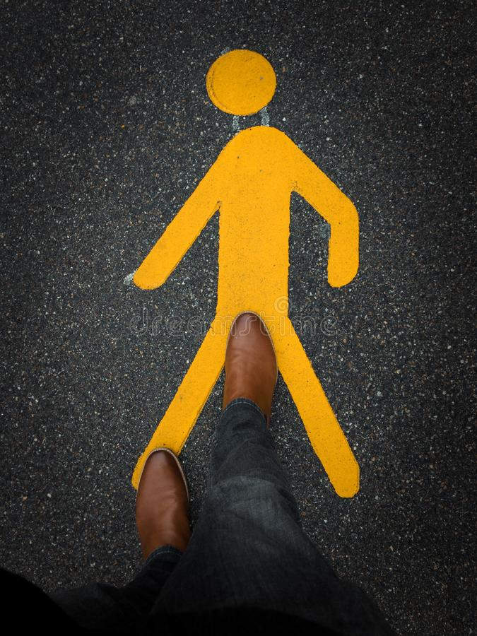 Pedestrian sign on pavement with brown leather boot royalty free stock photography