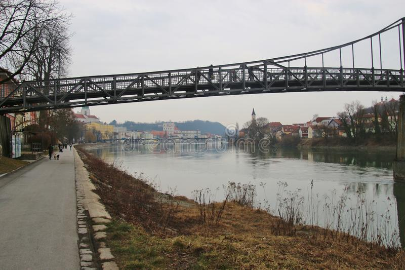 The pedestrian steel bridge Innsteg or Fünferlsteg in Passau, Germany. It connects the old town of Passau and the district Innstadt. The cityscape of Passau stock photo