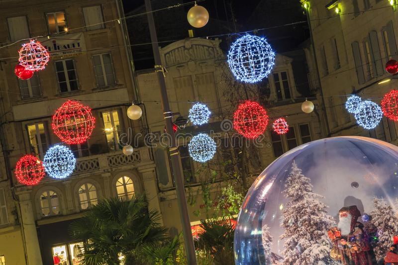 Pedestrian street illuminated by Christmas decoration with a big glass ball in the foreground stock photo