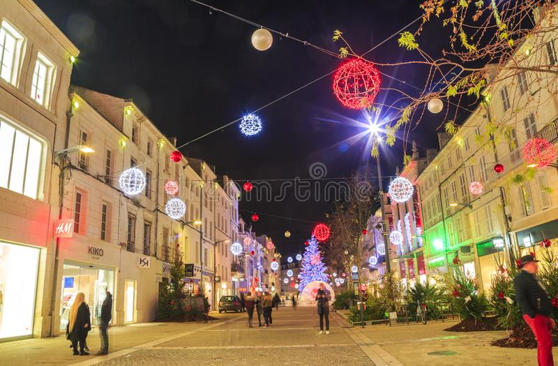Pedestrian street illuminated by numerous Christmas decoration in the city center of niort stock images