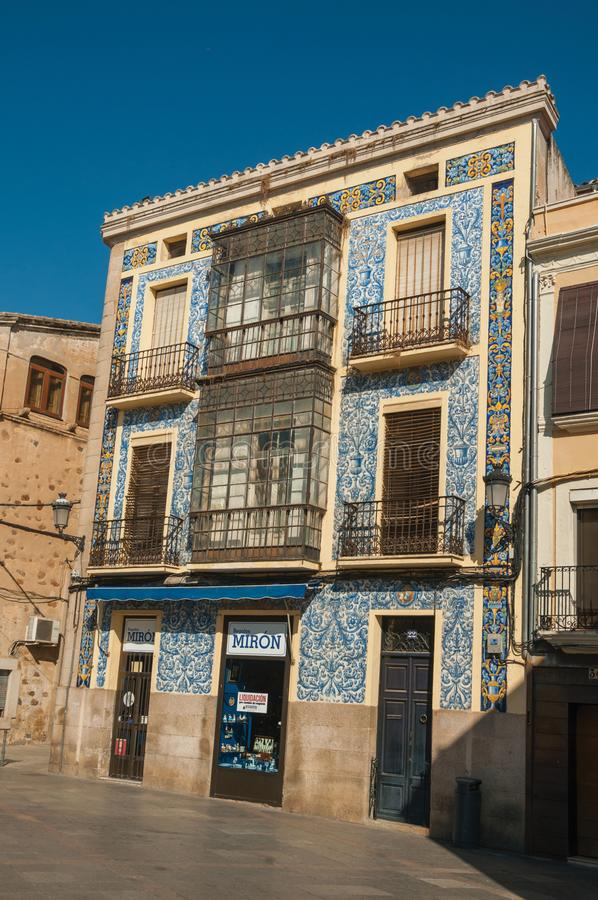 Pedestrian street and old building covered by colorful ceramic tiles in Caceres. Caceres, Spain - July 03, 2018. Pedestrian street and old building covered by royalty free stock image