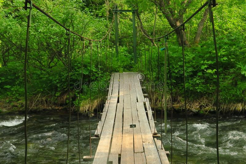 Pedestrian suspended wooden bridge over mountain river royalty free stock images