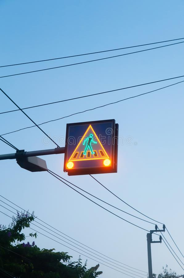Pedestrian traffic sign with glowing green light and save to move against blue sky stock photo