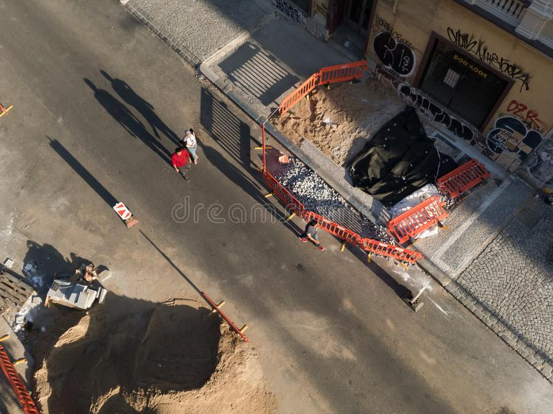 Pedestrian are walking on dug up street. PRAGUE, CZECH REPUBLIC / CZECHIA -JULY 9, 2018: Pedestrian are walking on dug up road. Street is under construction stock photography