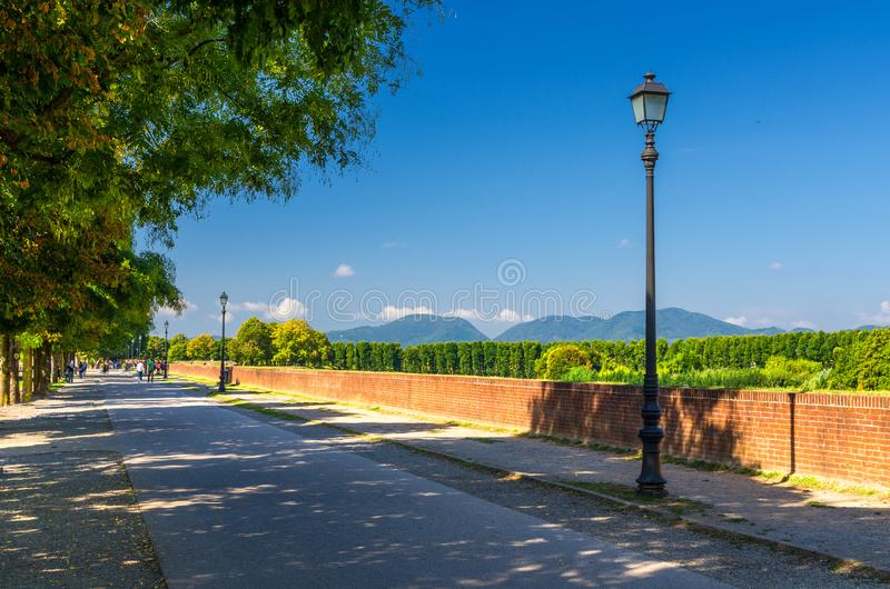 Pedestrian walking path street with lamps on defensive city wall in clear sunny day with Tuscany hills and mountains and clear blu. E sky background, Lucca royalty free stock images